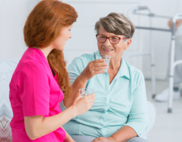 Young nurse drinking water and chatting with friendly senior woman