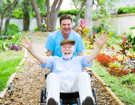 Caring nursing home orderly pops a wheelie with an elderly man's wheelchair