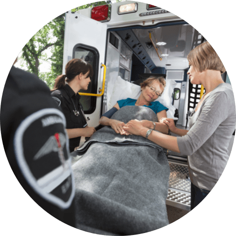 Senior women being loaded onto ambulance with caregiver at side