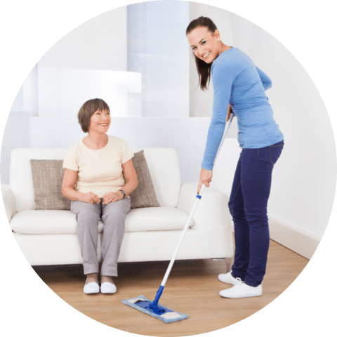 Portrait of caretaker cleaning floor with mop while senior women sitting on sofa at nursing home
