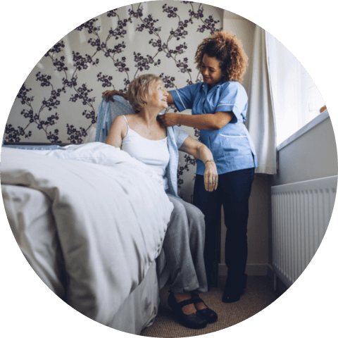 Caregiver helping a senior women get dressed in her bedroom