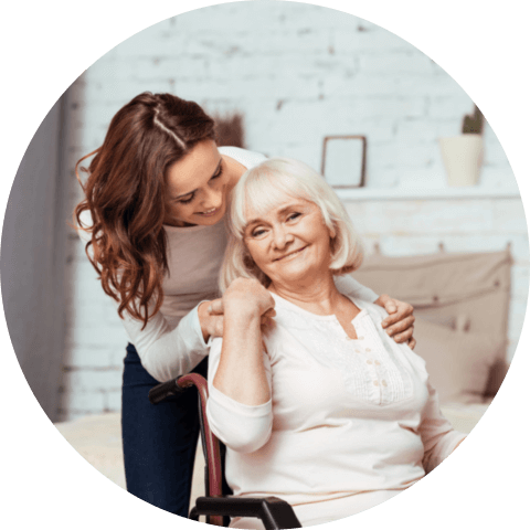 Pleasant elderly women smiling and sitting in the wheelchair with her caregiver